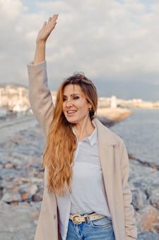 魅力的な女性が立って海辺で手を振っていて、昼間は興奮しているように見えます。