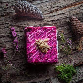 Сельдь под шубой из филе сельди с салатом, отварной картофель, свекла, морковь, свежий лук и майонез на деревянной коре