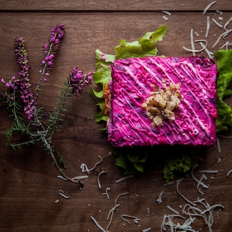 Крупная сельдь под шубой филе салатной соли, отварной картофель, свекла, морковь, свежий лук и майонез на деревянном столе