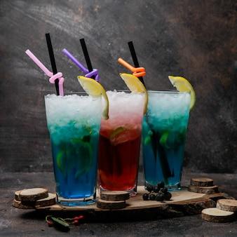 Алкогольные коктейли крупным планом, бокалы из голубой лагуны, коктейль с лимоном и бокал с виски на деревянной подставке