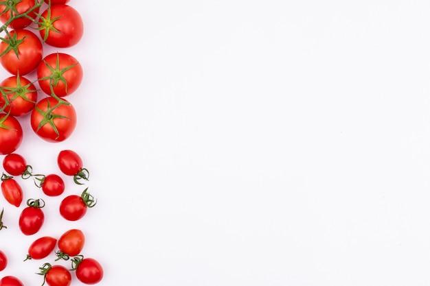 フレーム境界線の白い表面の左側にある新鮮な赤いトマトは、トマトを広げた