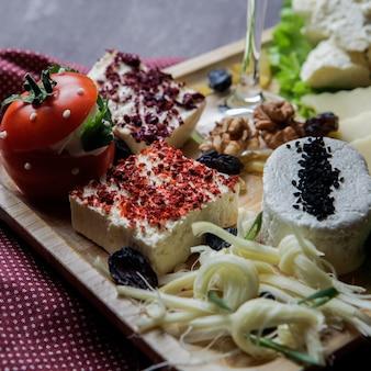 Крупный план нарезки сыра различными видами сыра, орехов, изюма, помидоров