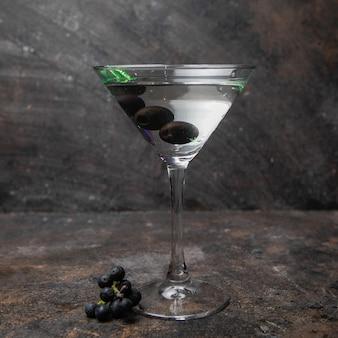 Боковой вид мартини в бокале с оливками