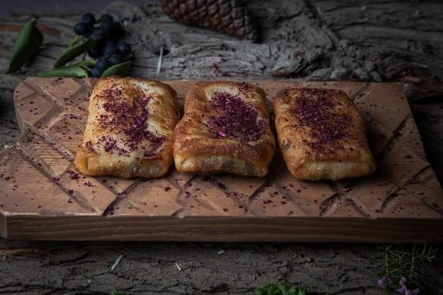 水平木の樹皮の木製スタンドに自家製の肉とサイドビューのパンケーキ