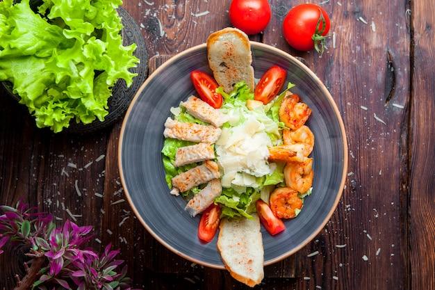 トップビューシーザーサラダチキンとエビのグリルチキンの胸肉、エビ、トマト、プレートの新鮮なサラダ