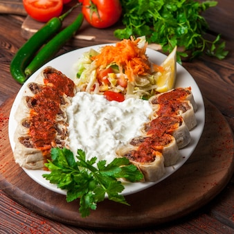 Сверху бейти шашлык с йогуртом и лимоном и салатом в белой тарелке