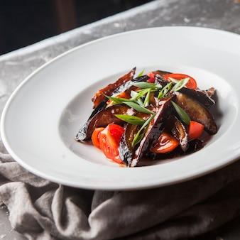 Сверху жареный баклажан с помидорами и нарезанным зеленым луком и тряпкой в круглой белой тарелке