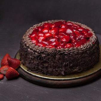 Сверху клубничный торт с клубникой в лотке