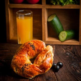 Бублик с оливками и апельсиновым соком и огурцами в таблице