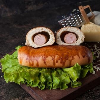 Булочка с салатом и хот-догом и сыром на деревянной доске
