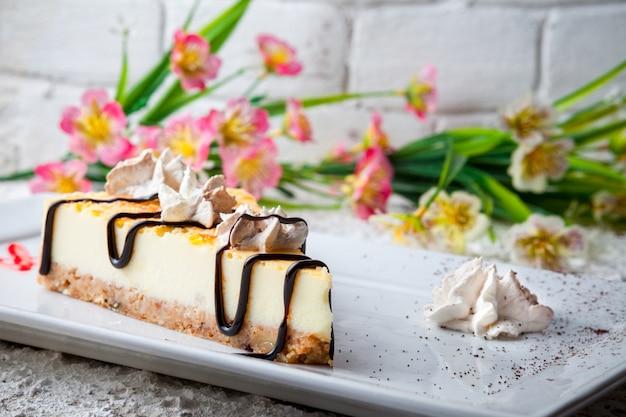 Чизкейк с цветами и сливками в белой тарелке