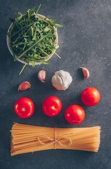 緑、トマト、ニンニク、灰色の織り目加工の背景、上面にいくつかのスパゲッティパスタ。