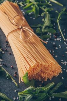 Некоторые макароны спагетти с зелеными на сером фоне текстурированных, высокий угол обзора.