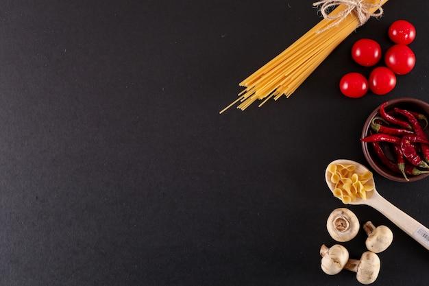 黒の表面にコピースペースを持つ乾燥赤唐辛子きのこトップビューのスパゲッティ