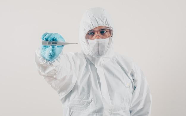 立っていると、マスク、医療用手袋、防護服の明るい背景に温度計を保持している医師。コロナウイルス