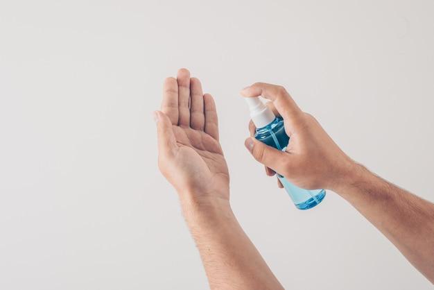 白い背景で手を消毒する男性。