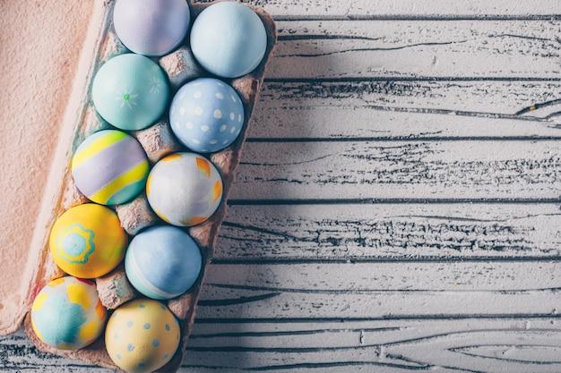 Пасхальные яйца в картонной коробке на легких деревянных фоне.