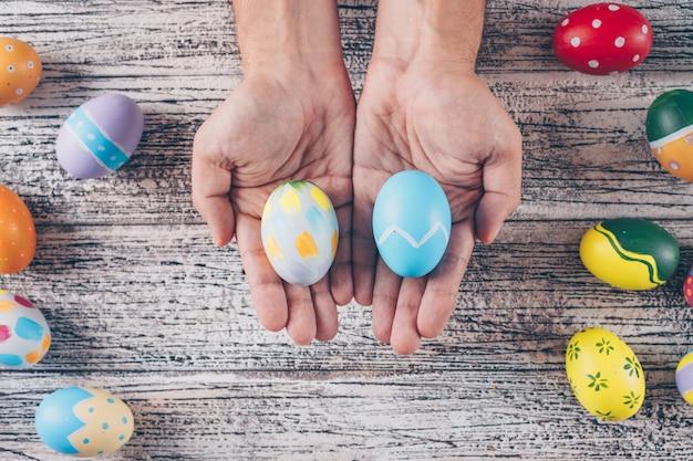 Пасхальные яйца в руках человека на деревянных фоне.