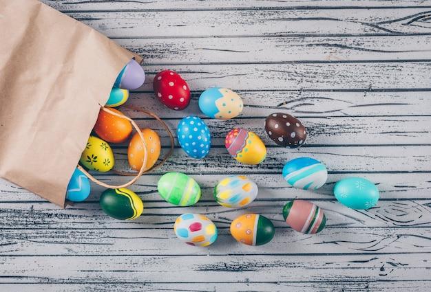 Взгляд сверху пасхальные яйца приходя из бумажной сумки на светлой деревянной предпосылке.