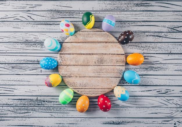Взгляд сверху пасхальные яйца в шаре с круговой древесиной на светлой деревянной предпосылке.