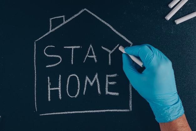 黒を描く家の中のチョークで家にいて手袋を書く男性