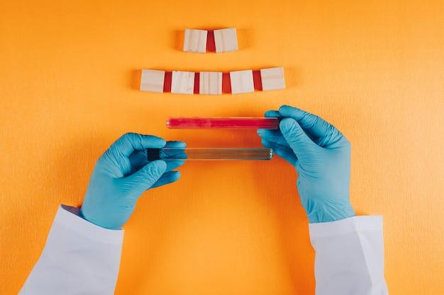 Набор деревянных элементов и доктор, держа лабораторные флаконы в обеих руках