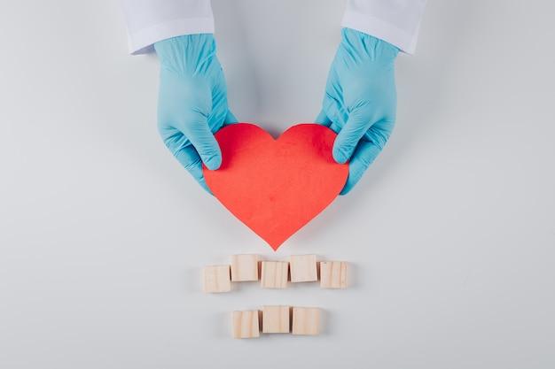 白の木製のブロックを持つ男性の手の中のいくつかの心