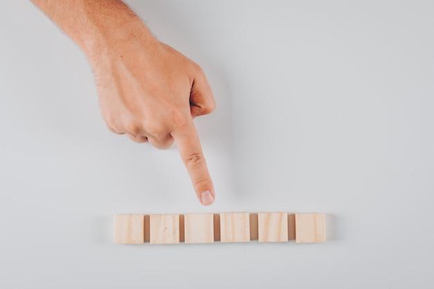 Какой-то человек, указывая на деревянные блоки на белом