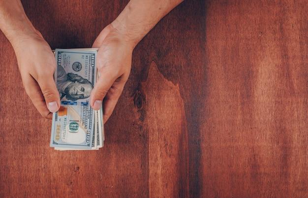 Вид сверху мужчина держит сто долларовых купюр на деревянном