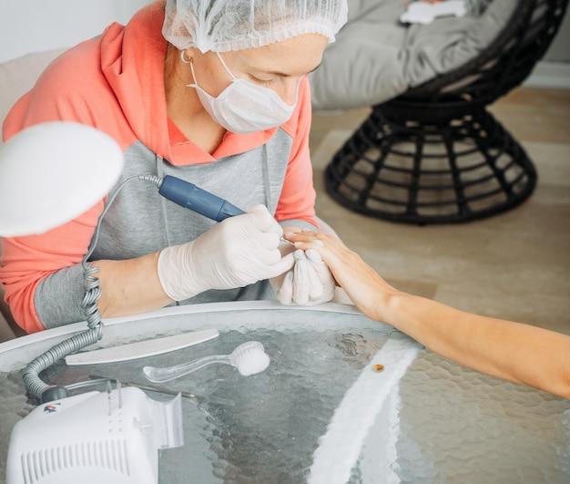 Женщина, получающая маникюр от женщины в перчатках и маске в салоне красоты в дневное время