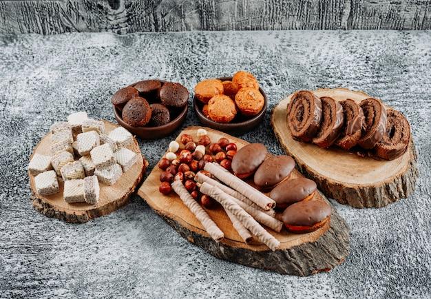 Высокий угол обзора чай с вафлями и пирожными на тарелках и разделочной доской на светло-текстурированной