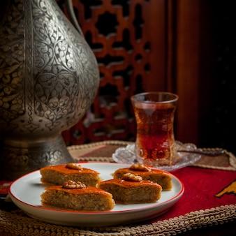 Вид сбоку пахлава с бокалом чая и железный старинный чайник в белой тарелке