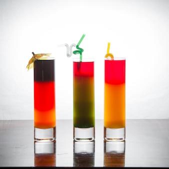 Вид сбоку коктейльные снимки с коктейльным зонтиком и соком соломы в столе