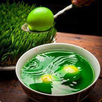 Вид сбоку крашеные яйца с семени и воды в белой тарелке