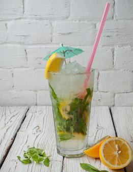 ガラスのカップにレモンとジュースのストローミントと側面図モヒート