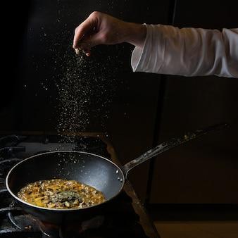 サイドビューキノコフライパンでストーブとドライミントと人間の手で揚げる