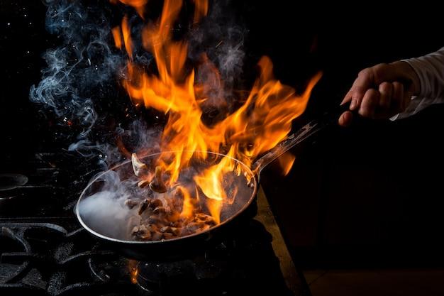 Вид сбоку жарки грибов с плитой и огнем и человеческой рукой в кастрюле