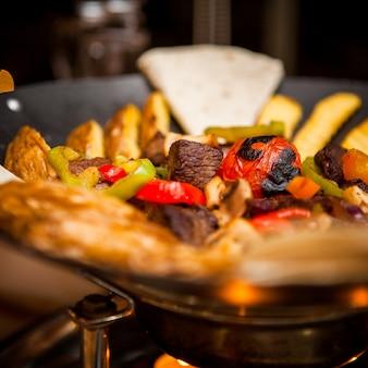 Боковой вид саквояж с мясом и жареной картошкой в столе на ресторане