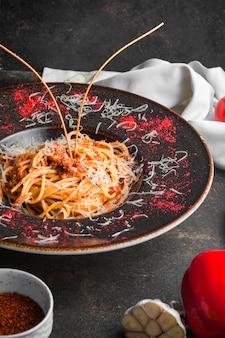 Вид сбоку спагетти с мясным фаршем и чесноком в круглой тарелке