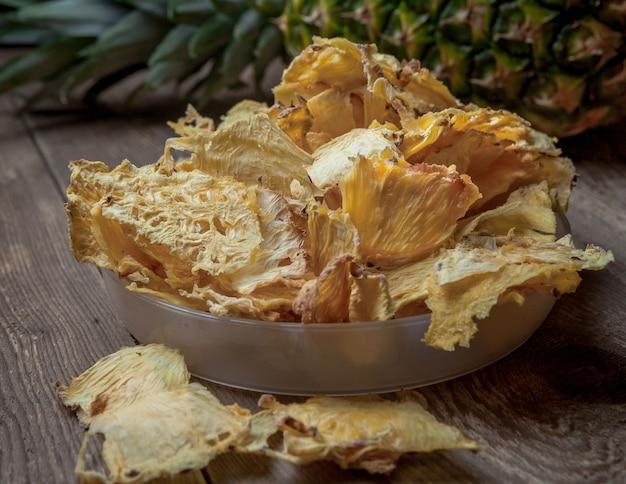 サイドビューのクローズアップの乾燥パイナップルと新鮮なパイナップルの木製テーブル