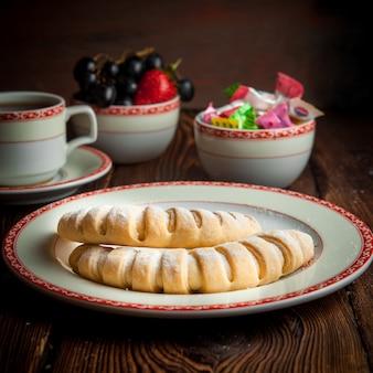 サイドビュークローズアップの自家製クッキー、紅茶、お菓子、木製のテーブルの上の果実