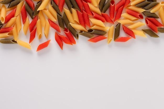 コピースペースを持つ生の色パスタ緑黄色と赤ペンネパスタ