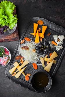 Вид сверху сырное ассорти с виноградом и орехами и медом в лотке