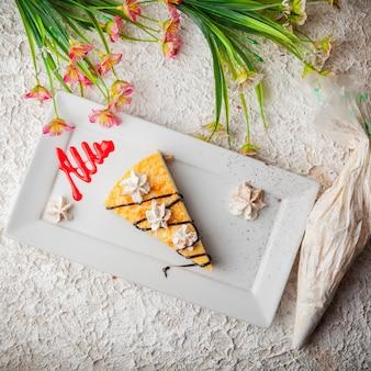 花と白い皿にクリームとトップビューチーズケーキ