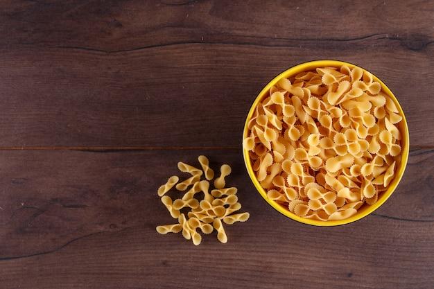 Сырые макароны в желтой миске сверху на деревянной поверхности