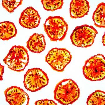Вид сверху узор кусочки сушеных помидоров на ярко-белом фоне
