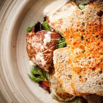 Жареное куриное филе сверху с крекерами и зеленью в круглой тарелке