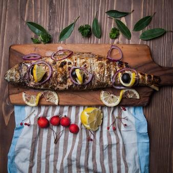 Вид сверху жареная рыба с лимоном и райскими яблоками и салфетками в разделочной доске