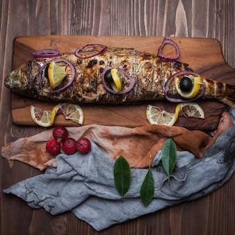 Вид сверху жареная рыба с лимоном и райскими яблоками и луком в разделочной доске