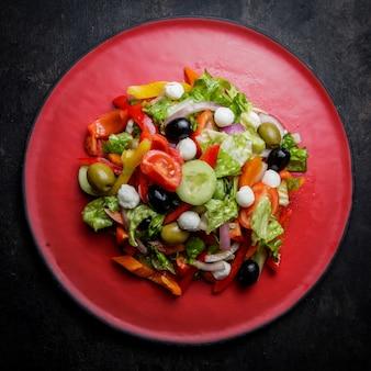 Вид сверху греческий салат с помидорами и оливками и листьями салата в красной тарелке